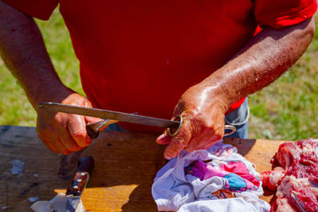 Butcher is sharpening knife before cutting the raw pork meat into smaller pieces on a wooden board. Stok Fotoğraf