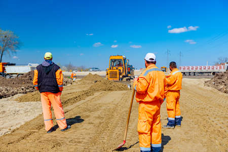 Workers stand and watch earthmover with caterpillar that is moving earth outdoors. 版權商用圖片