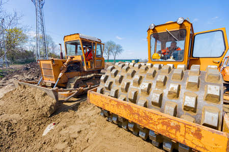 Road roller with spikes and bulldozer are compacting, leveling sand for road foundation at building site.