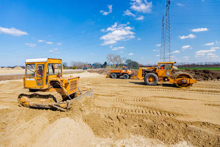 Road roller with spikes, bulldozer and truck with mounted plate vibration compactor are compacting, leveling sand for road foundation at building site. 版權商用圖片