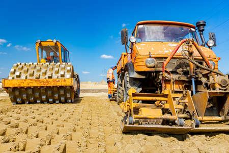 Road roller with spikes and truck with mounted plate vibration compactor are compacting, leveling sand for road foundation at building site.