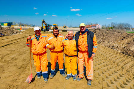 Zrenjanin, Vojvodina, Serbia - April 05, 2021: Construction smiling workers are posing, resting and enjoying at construction site. 新聞圖片