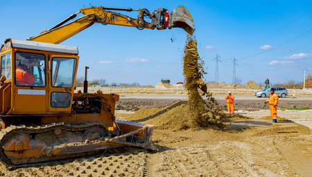 View on bulldozer that is leveling sand for road foundation at building site, mechanization. 版權商用圖片