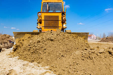 Earthmover with caterpillar is moving earth outdoors.