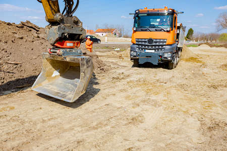 An excavator pulls a tipper truck with a cord to help him to get out from sand at building site.
