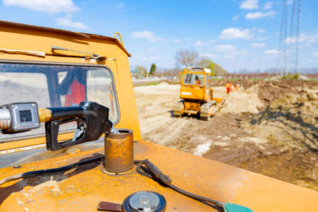 Fuel pump gun inserted in the reservoir of construction machine, pour gasoline, diesel in the vehicle. 版權商用圖片