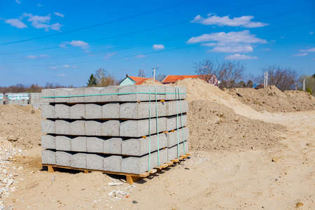 Stack of packed border stones for asphalt road on wooden pallet at building site.