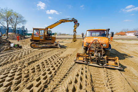 View on excavator and truck with mounted plate vibration compactor, as they are compacting, leveling sand for road foundation at building site, mechanization.