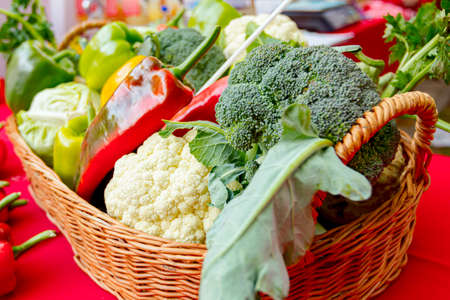Decorated basket with fresh vegetables for sale placed on stall, available at flea market.