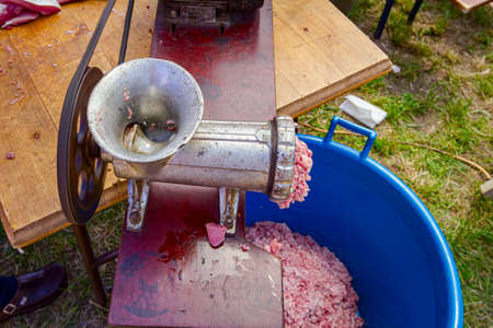 Above view on meat grinder machine, forcemeat process for making sausages at outdoor kitchen.