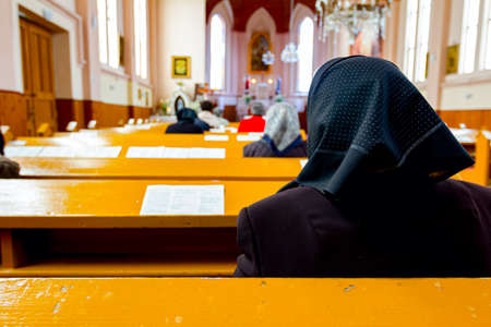 Female believers are praying with their priest at Sunday morning in old and small Catholic Church. 版權商用圖片