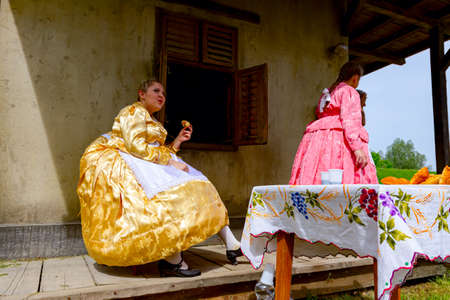 Ivanovo, Vojvodina, Serbia - April 17, 2016: Two girls wearing a traditional folk costume, are enjoy eating fresh baked donuts with sugar at outdoor in shade.
