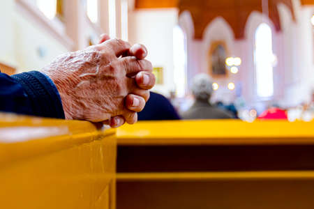 Prayer's hands as they are praying with their priest at Sunday morning in old and small Catholic Church. 版權商用圖片
