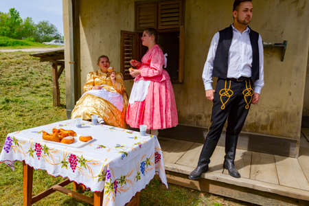 Ivanovo, Vojvodina, Serbia - April 17, 2016: Two girls with one guy wearing a traditional folk costume, are enjoy eating fresh baked donuts with sugar at outdoor in shade.