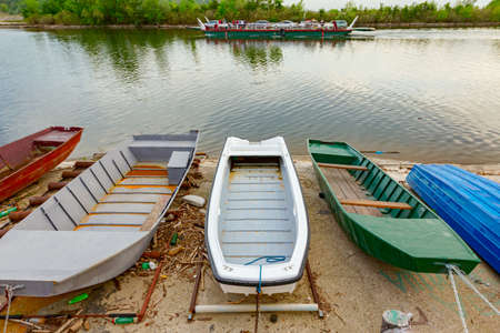Painted boats are dry docked over coastline covered with concrete.