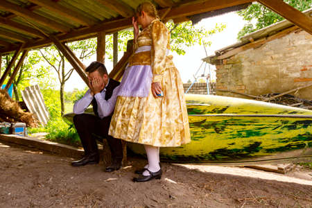Ivanovo, Vojvodina, Serbia - April 17, 2016: Girl make jokes with young man who is sitting on wooden stump wearing a traditional folk costume in ancient, old wooden stable.