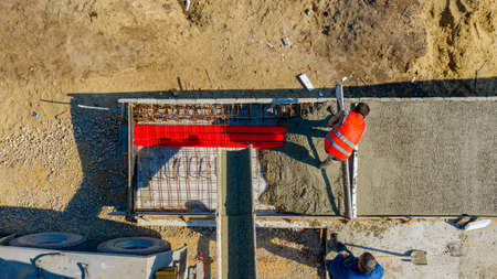 Above top view, overhead on construction workers are leveling fresh concrete with metal lath in square trench after pouring from mixer truck.