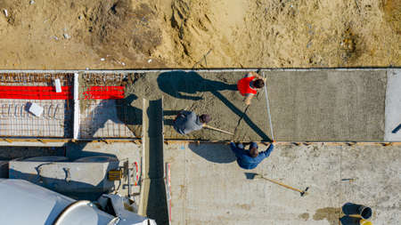 Above top view, overhead on construction workers are using rake to spreading and metal lath for leveling fresh concrete in square trench after pouring from mixer truck.