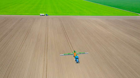 Above view, overhead view on tractor until spraying big endless farmland dragging mounted wide agricultural sprayer on a sowed field.