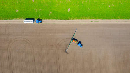 Above top view, overhead view on tractor until spraying big endless farmland dragging mounted wide agricultural sprayer on a sowed field. 版權商用圖片