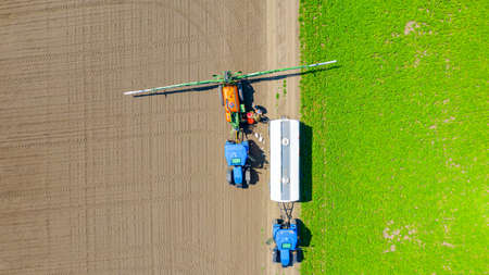 Above top view, overhead view on two farmers as they preparing, mixing chemicals and filling sprayer's reservoir with water from agricultural cistern.