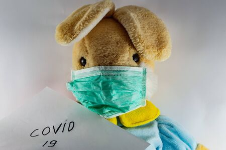 In images rabbit in a protective medical mask lies in a crib on a white bed. The toy got sick. Playing doctor. Protection from viruses, influenza, coronavirus for children