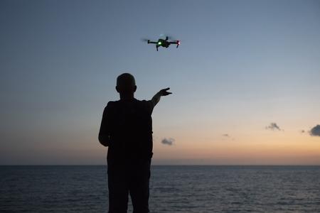 A man runs a quadcopter over the ocean. Selective focus.