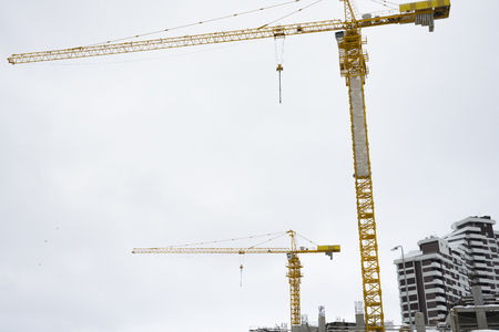 Multi-storey construction. Two cranes on white background.  In the background is an unfinished building. Copy space.