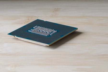 A computer processor on a wooden background. Side view. Close up.