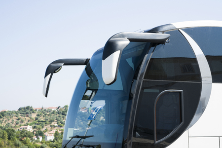 The front part of the tourist bus on the background of the village. The image shows a windshield and two mirrors.