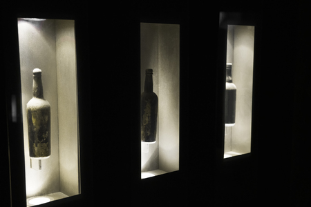 Museum of port wine. Three old bottles stand in a niche behind the glass.  Selective focus. Copy space.