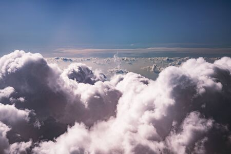 Cumulus clouds are pale pink against a blue sky. The view from the top. Stok Fotoğraf