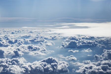 Sky with clouds. Under the clouds, the mountainous landscape and the ocean shore are faintly visible. The view from the top.