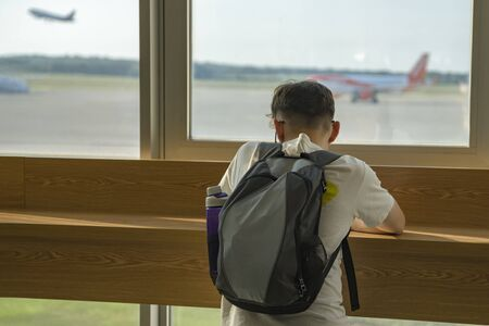 A teenage boy with a backpack is behind the counter at the window in the airport building. Outside the window takes off the plane. Selective focus. Copy space.