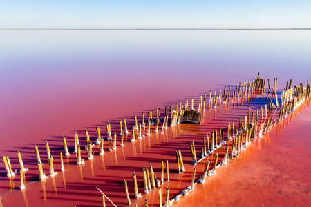 A fantastic pink-orange salt lake with salt crystals on wooden pillars. Shooting from a drone. Copy space. Stock Photo