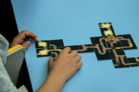 A cut-off image of a child collecting a puzzle picture on the table. The blue background shows the hands of a child and a few connected puzzles. Selective focus.