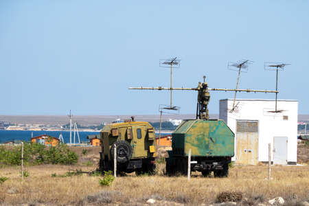 Mobile military radar station on wheels for detecting aerodynamic and ballistic objects. The military facility is located in the steppe on the seashore.