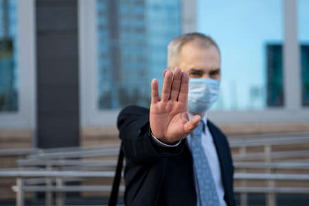 An adult male wearing a medical mask with his right arm outstretched. The image of the man and the background behind him is blurred, the emphasis is on the palm of the hand. Selective focus.