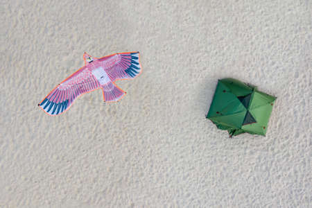 A lonely green tourist tent and a kite in the form of a pink bird of Paradise on a white sand background. Shooting from the air.