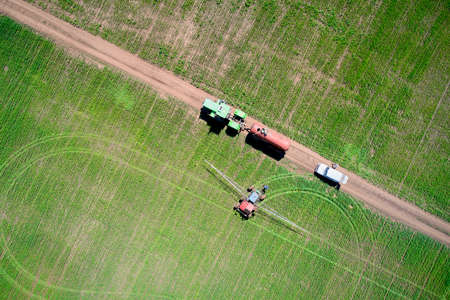 Treatment of the field with herbicides. A tractor with a spray gun drove up to a tractor with a barrel on the road to fill up chemical reagents. Shooting from a drone.