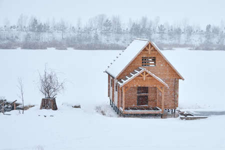 A small wooden house on stilts by a frozen river. A hole has been cut in the ice near the house. Copy space.