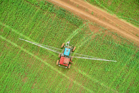 Seasonal agricultural work. Protection of the field from weeds, diseases and pests. The agronomist refills special equipment with pesticides. Shooting from a drone. Copy space.