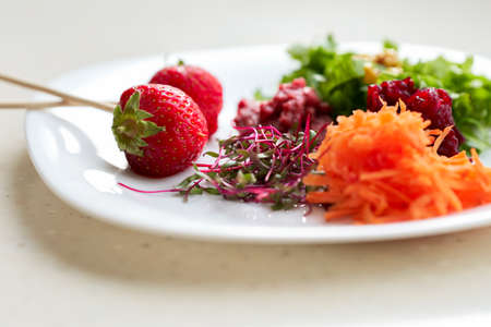 A white plate with vegetables, chard sprouts and strawberries in close-up.