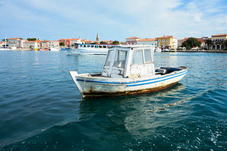 Funny old boat in the water area of Porec, Croatia. In the background, the old town embankment. Copy space.