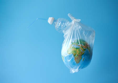 A plastic bag with a globe and a plastic bottle on a blue background. Concept: planetary plastic pollution. Copy space.