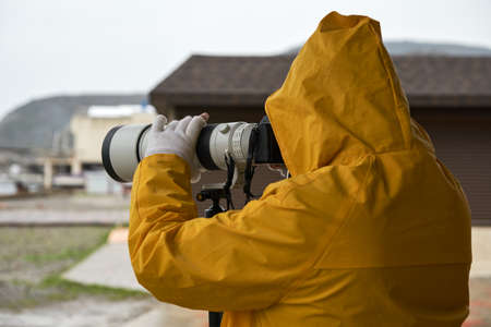 A man in a yellow raincoat takes photos with a long-focus lens fixed on a monopod tripod. Rear view.