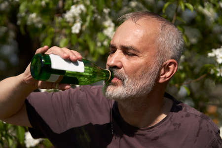 An adult man on a hot day in nature drinks water from a glass bottle. Selective focus. Stock Photo