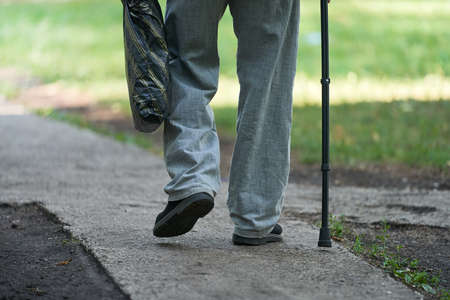 An elderly man slowly walks along the path leaning on a cane. In his hand he holds a plastic bag with the purchased products.