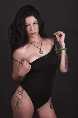 Tattooed brunette in black swimsuit on black background Stock fotó