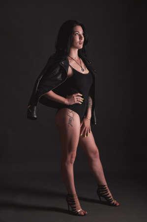 Tattooed brunette in black swimsuit on black background Archivio Fotografico